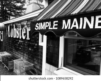 "Wells, Maine, USA: May 11, 2018: A black and white photo of the front of a rustic seafood restaurant on the Maine coast with signs that say ""Lobster"" and ""Simple Maine with lobster traps."
