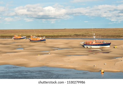 Wells next the Sea, Norfolk, UK 10/13/2019 Three vintage lifeboats stranded at low tide