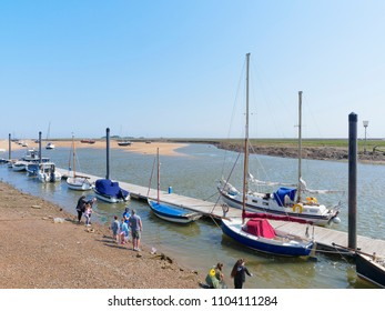 Wells-next-the-Sea, England - May 27 2018: At low tide in the estuaty at Wells-next-the-Sea yachts and motor boats are beached on the sand. At the waters edge a small group of people fish for crabs.