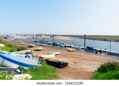 Wells-next-the-Sea, England - May 27 2018: At low tide in Wells-next-the-Sea boats sit beached on the sand. A small group of people fish for crabs at the waters edge.