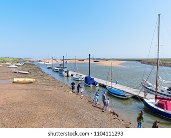 Wells-next-the-Sea, England - May 27 2018: At low tide in Wells-next-the-Sea yachts and motor boats are beached on the sand. At the waters edge a small group of people fish for crabs.