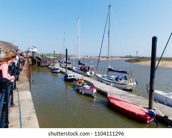 Wells-next-the-Sea, England - May 27 2018: On a bright spring day holidaymakers line the quay at Wells-next-the-Sea. Some are fishing for crabs others are watching. Boats are moored to a wooden jetty.