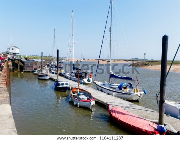 Wells-next-the-Sea, England - May 27 2018: On a bright spring day holidaymakers line the quayside at Wells-next-the-Sea. Some people are fishing for crabs. Boats are moored to a wooden jetty.
