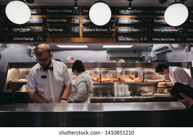 Wells-next-the-sea, UK - April 20, 2019: Staff serving fish and chips inside popular French's fish and chip shop in Wells-next-the-sea, a seaside town and port in Norfolk, UK, famous for its beach.