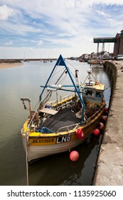 WELLS-NEXT-THE-SEA, UK - APRIL 4, 2011: Small fishing trawler moored at the quayside in Wells in Norfolk, England. The distinctive, overhanging gantry of the granary can be seen behind