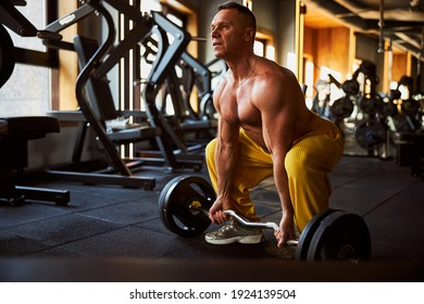 Well-trained athlete squatting before lifting a barbell with heavy weights at the gym