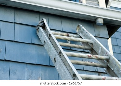 well-used extension ladder balanced against the back of a house, poised to allow access to the house gutters.