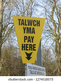 Welsh Parking Meter Pay Here Sign in Welsh and English, shallow depth of field, Wales Cardiff Winter 2019