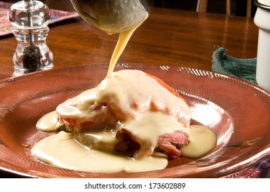 Welsh Rarebit (or Welsh Rabbit) ladling onto toast, ham, eggs, tomatoes
