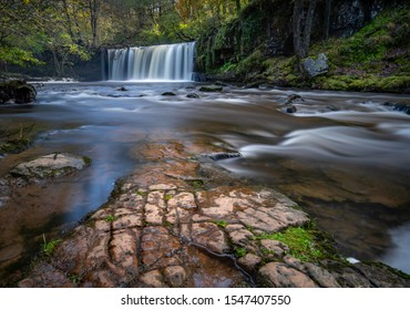 A welsh waterfall on the River Neath in the Brecon Beacons, South Wales, captured using a slow shutter speed. An outcrop of fractured rock fills the foreground as the smokey water flows over it.