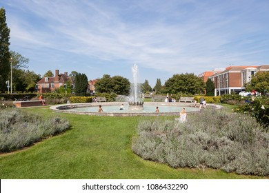 WELWYN GARDEN CITY, UK - AUGUST 28, 2017: Children paddling on a hot summer day in Parkway Fountain in The Parkway Gardens in the centre of Welwyn Garden City.