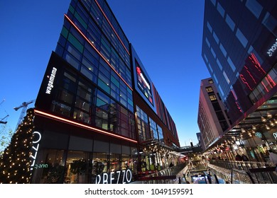 Wembley, London 15 Dec 2017: Night scene of modern office buildings with glass windows, shops and outlets at the ground floors