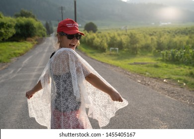 Wenatchee, Washington - July 4, 2019: Cute Republican woman wearing a MAGA hat (Make America Great Again) supporting President Donald Trump and his 2020 re-election campaign, smiles and poses