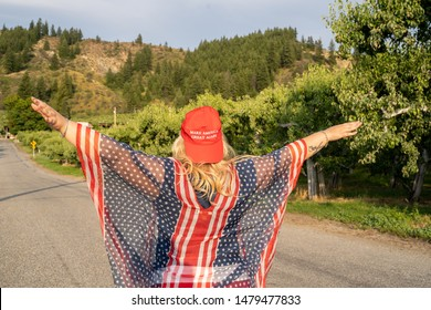 Wenatchee, Washington - July 4, 2019: Republican woman wearing a MAGA hat (Make America Great Again) supporting President Donald Trump 2020 re-election campaign, poses with arms raised in freedom