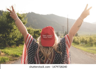 Wenatchee, Washington - July 4, 2019: Republican woman wearing a MAGA hat (Make America Great Again) supporting President Donald Trump and his 2020 re-election campaign, poses with arms raised