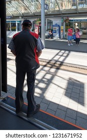 Wengen/Switzerland - August 26 2018: Ticket inspector in Wengen train station waiting for his train to leave. Wengen is a village in the Bernese Oberland in the canton of Bern.