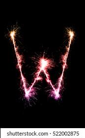 W,English alphabet from sparkler on black background,Alphabet big letter