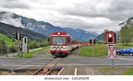 Wenns / Austria - July 22 2018: A train of the Pinzgauer Lokalbahn arrived at the railway station (bahnhof) of Bramberg Wenns in the Pinzgau with beautiful mountains at the background