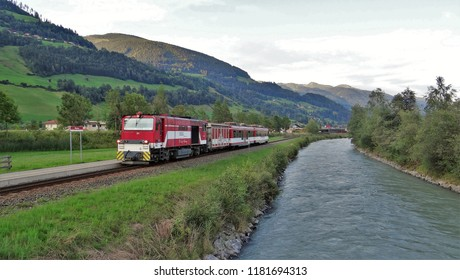 Wenns / Austria - July 26 2018: A train of the Pinzgauer Lokalbahn at the railway station of Bramberg Wenns in the Pinzgau with beautiful mountains at the background and the river the Salzach