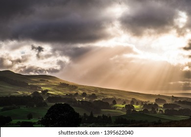 Wensleydale, Yorkshire Dales National Park, North Yorkshire, England, Britain, August 2016, sun shining through dark clouds illuminating landscape as rays