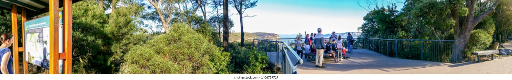 Wentworth Falls, Australia - May 16, 2016: Panorama of the Jamison Lookout, with visitors on seats and a lady studying a directory board. Jamison Valley is behind the lookout area. UNESCO listed site.