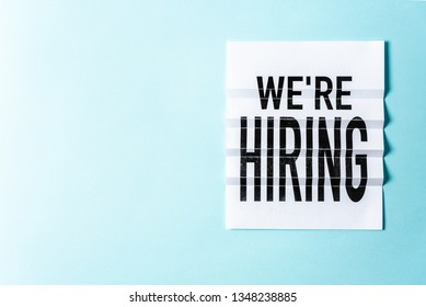 """""""We're hiring"""" lettering on textured blue background with blank or negative space for text. Job board design, template. Concept of recruiting for business."""