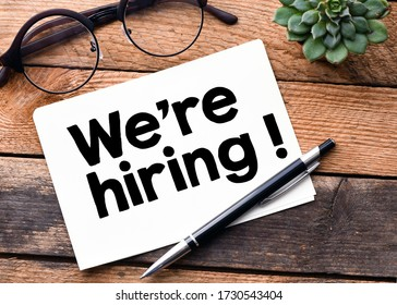 We're Hiring words written on a white sheet and a wooden background. Concept in business.