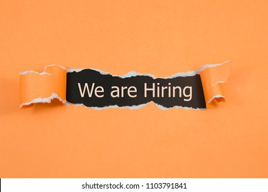 We're Hiring written under torn paper. Human resource concept, strategy, plan, planning.