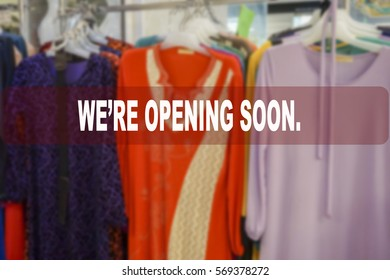 We're opening soon text on blur shopping complex background.