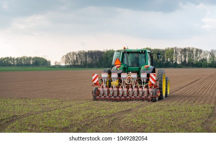 WERKENDAM, NETHERLANDS - APRIL 4, 2017: Unidentified driver in a tractor looks behind at the sowing machine as he drives over the cultivated field. It is spring and the growing season starts again.