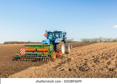 WERKENDAM, NETHERLANDS -MARCH 20, 2018: Unidentified farmer prepares the seedbed and sows brewery barley in one operation with a harrow and a mechanical seed drill both connected to the tractor.