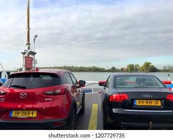 Werkendam, the Netherlands - October 20, 2018: Dutch motorists on the ferry boat Biesbosch between Werkendam and Dordrecht against a partly clouded sky.
