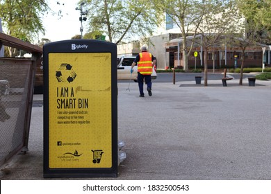 Werribee, Vic/Australia - Oct 3 2020: Council worker picking up rubbish with  solar powered smart bin in foreground