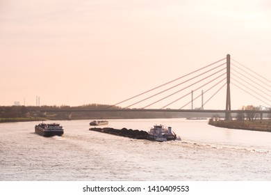 WESEL, GERMANY - FEBRUARY 23, 2019: Heavy traffic of barges and container ship on the Rhine river with the Lower Rhine Bridge in the background