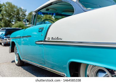 Wesley Chapel, North Carolina - July 27, 2019: Onlookers pass a vintage Chevy Bel Air on display at the Rock N Roller Event at Dogwood Park