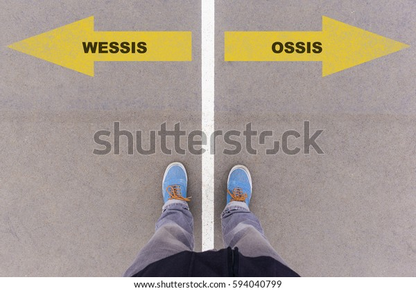Wessis / Ossis (German for West and East Germans) direction sign text on asphalt ground, feet and shoes on floor, personal perspective footsie concept