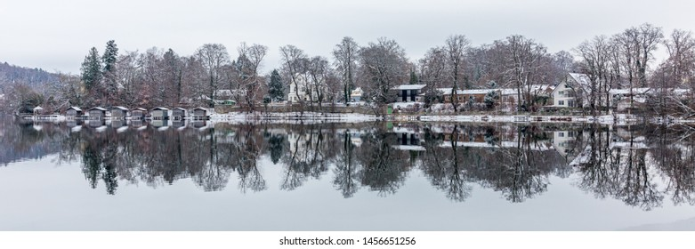 WESSLING, BAVARIA / GERMANY - December 16, 2018: Panorama view of Lake Wessling (Weßlinger See). Reflection of trees and houses in the water. Romantic winter landscape - great travel destination.