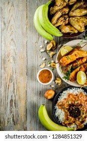 West african food concept. Traditional Wset African dishes assortment - peanut soup, jollof rice, grilled chicken wings, dry fried bananas plantains, nigerian chicken kebabs, meat pies, top view