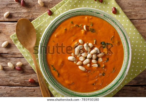 West African peanut soup with kale closeup on a plate on a table. horizontal top view from above
