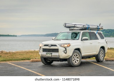 West Alton, MO, USA - July 28,2018: Toyota 4Runner SUV (2016 trail model) with a  stand up paddleboard on roof rack at a shore of Mississippi River at Lincoln Shields Recreation Area