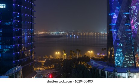 West Bay area from top in Doha timelapse, Qatar. Gulf between two Illuminated modern skyscrapers aerial view from rooftop at night