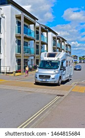 West Bay, Dorset / England - 7/20/2019: A stylish Italian built & registered Laika motorhome on tour in the UK and here visiting the harbour in West Bay, passing a modern apartment block.