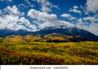 West Beckwith Mountain on sunny autumn afternoon with valley of aspen trees changing for the season