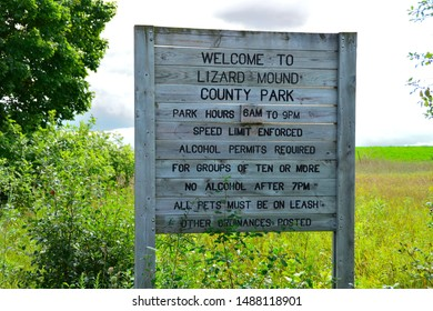 West Bend, Wisconsin / USA - August 23, 2019: The old sign along the road as you enter Lizard Mound County Park Native American Burial Grounds diplays the rules and ordinances.