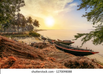 West Bengal, India, December 25,2018: Sunrise at the banks of the Rupnarayan river with fishermen and fishing boats with scenic rural landscape at Deulti, West Bengal India