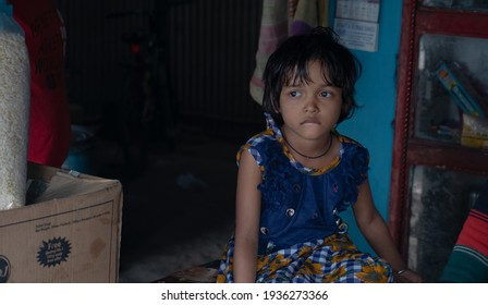 West Bengal, India - Feb 15, 2021: Rural little Indian girl wearing a colorful frock and sitting isolated in a room with an unconscious candid  expression on her face | lifestyle in India