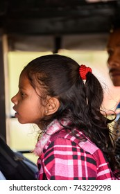 WEST BENGAL, INDIA - MAR 12, 2017: Unidentified Indian little girl in plaid shirt with red scrunchy on her hair opens her mouth.