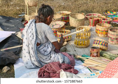 West Bengal, India, November 22,2019: Old woman slicing bamboo cane strands for making baskets to sell for a living at a village in Bolpur, West Bengal