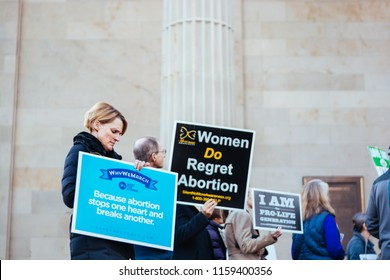 West Chester, PA USA January 21,2018: Woman and small group holding multiple pro-life protest signs on courthouse steps.