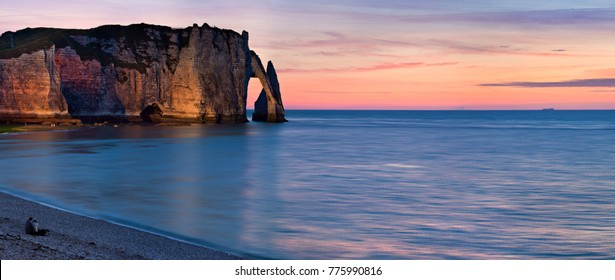 West coast of France. Cliffs of Etretat, Lovely couple sitting on the beach and meeting sunset.